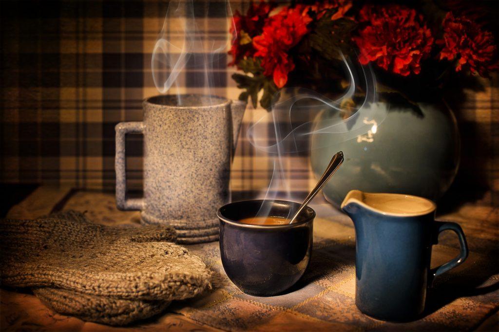 Horká káva s vlněnými rukavicemi a kvetinou na stole