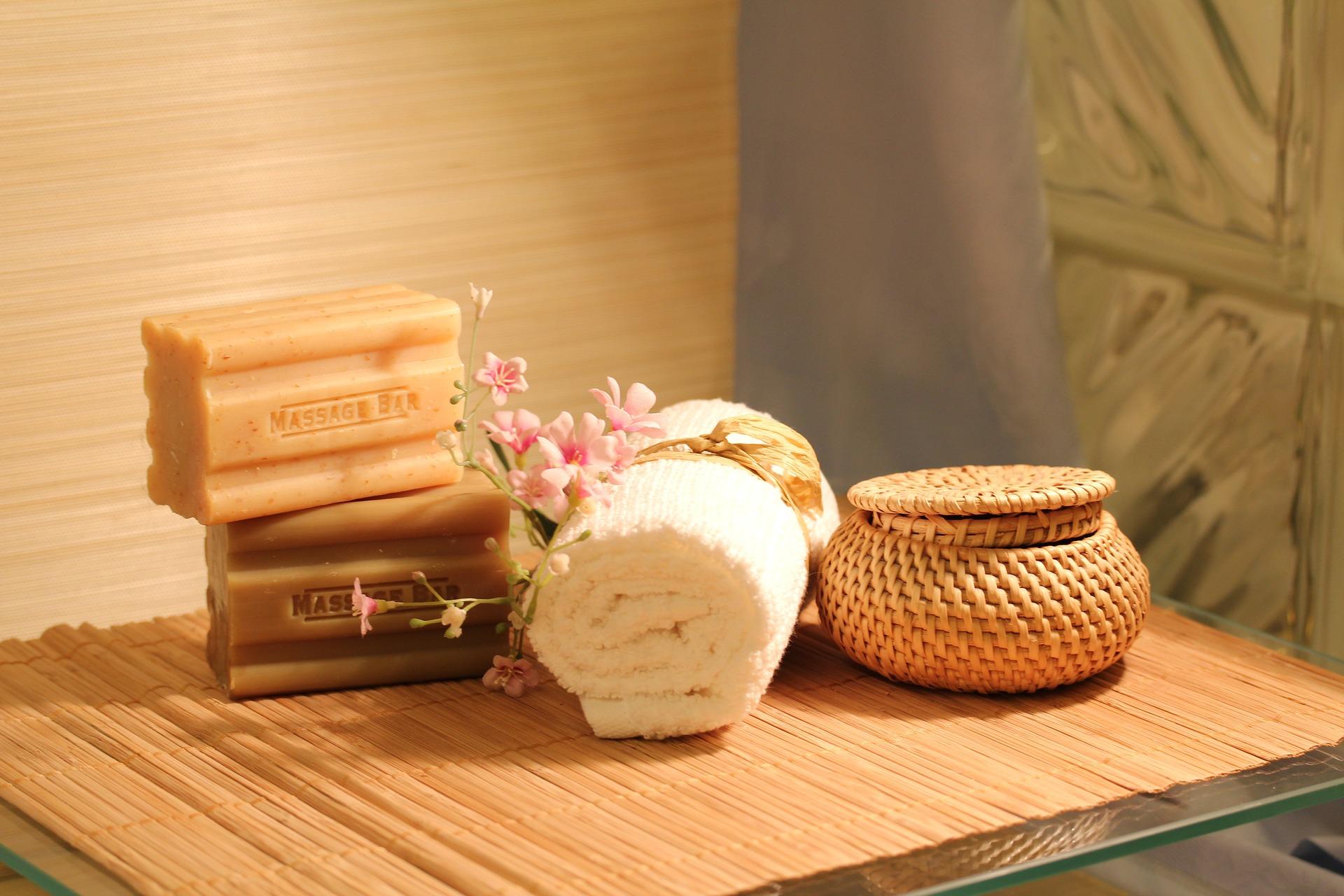 Prostor pro masáž, kompozice ručníku a mýdel na dřevěném stole osvíceném slunečními paprsky.