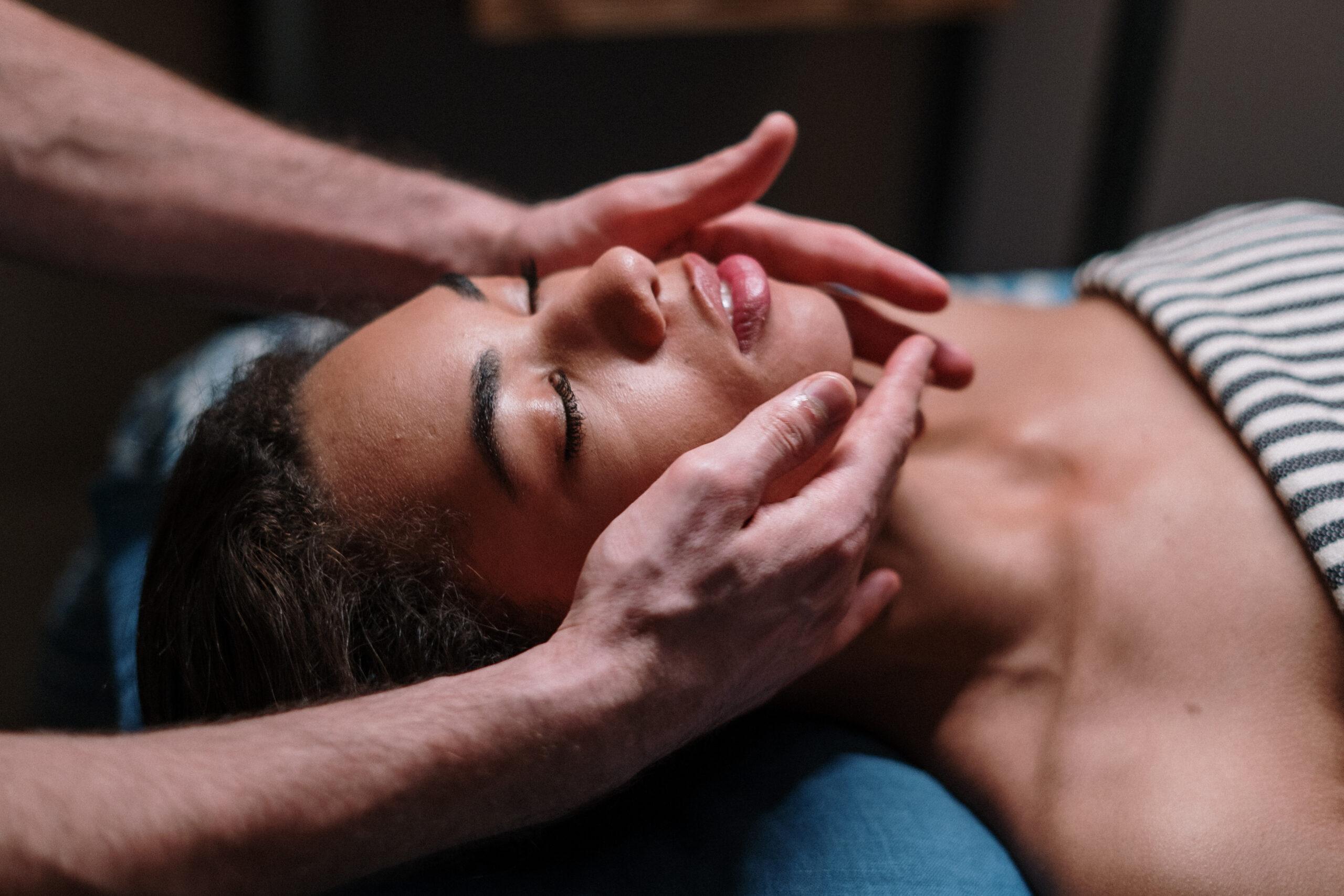 Masáž oblyčeje ženy ležící na modro-bílé látce