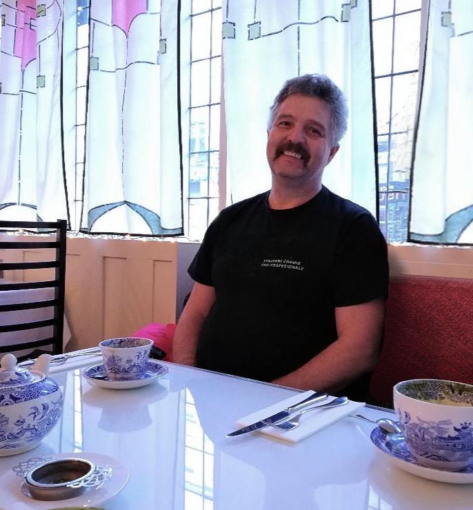 Masér Jirak sedící v kavárně navržené architektem Renniem Mackintoshem