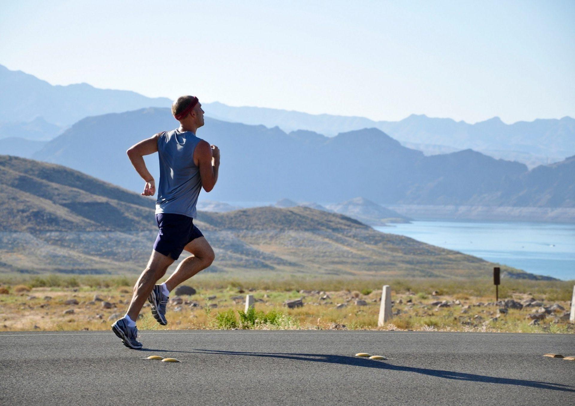 Běžec běžící po silnici, v pozadí je jezero a hornatý terén
